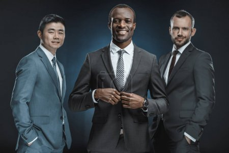 Photo for Portrait of multicultural smiling businessmen in suits looking at camera isolated on black - Royalty Free Image