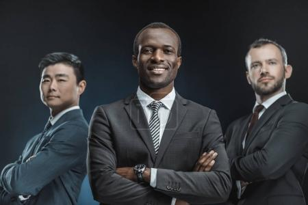 Photo for Portrait of multicultural group of businessmen in suits looking at camera isolated on black - Royalty Free Image