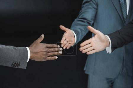 Photo for Partial view of multiethnic group of businessmen outstretching hands for handshake isolated on black - Royalty Free Image