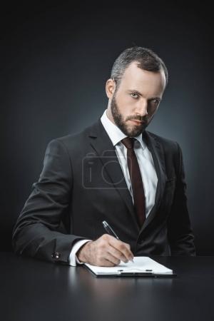 Photo pour Portrait d'un homme d'affaires confiant signant un document à table isolé sur noir - image libre de droit
