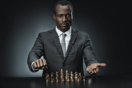 african american businessman holding chess figure
