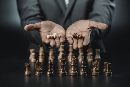 Photo for Cropped shot of african american businessman holding chess figures isolated on black - Royalty Free Image
