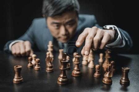 Asian businessman playing chess