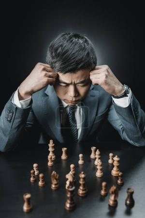 Photo for Focused asian businessman looking at chess pieces on table isolated on black - Royalty Free Image