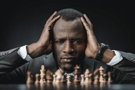 Photo pour Portrait de confuse confuse africain homme d'affaires américain tenant tête et en regardant d'échecs les chiffres sur la table isolée sur fond noir - image libre de droit