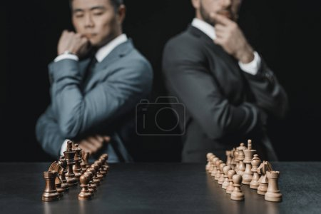 multiethnic businessmen looking at chess