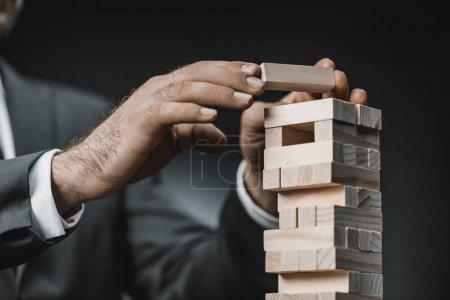 Photo pour Vue partielle de l'homme d'affaires en costume jouant bloque jeu bois - image libre de droit