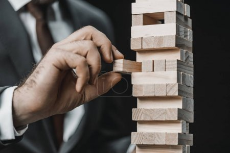 Photo for Partial view of businessman in suit playing blocks wood game - Royalty Free Image
