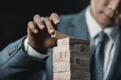 asian businessman playing blocks wood game