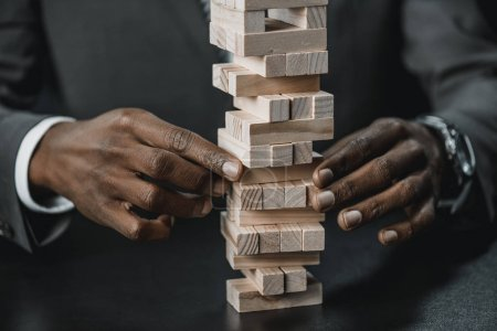 Photo for Cropped shot of african american businessman playing with blocks wood game - Royalty Free Image