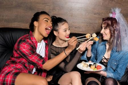 Multicultural women with sushi at hen party