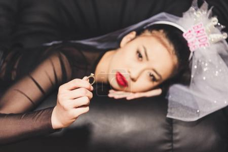 Photo for Selective focus of pensive asian fiance in veil holding wedding ring while lying on sofa - Royalty Free Image