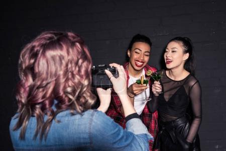 Foto de Amigo tomando foto de sonrientes amigos multiétnicos con cócteles en la fiesta - Imagen libre de derechos
