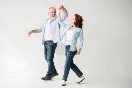 Photo for Smiling mature couple dancing and holding hands, isolated on white - Royalty Free Image