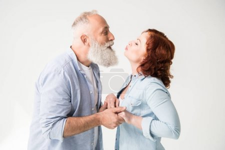 Photo for Happy mature couple kissing and holding hands, isolated on white - Royalty Free Image