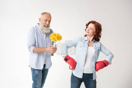Photo for Dissatisfied mature woman in boxing gloves and her husband with bouquet, isolated on white - Royalty Free Image
