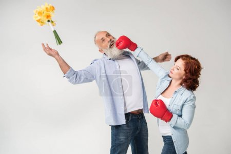 Photo for Mature woman in boxing gloves punching her husband, isolated on white - Royalty Free Image