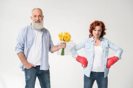 Dissatisfied mature woman in boxing gloves and her...