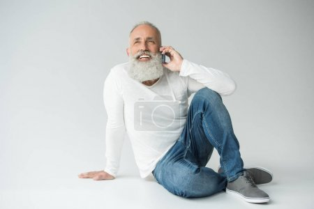 Photo for Smiling senior bearded man talking on smartphone, isolated on white - Royalty Free Image