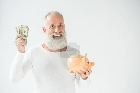 Foto de Sonriente hombre barbudo mayor con billetes de dólar y alcancía, aislado en blanco - Imagen libre de derechos