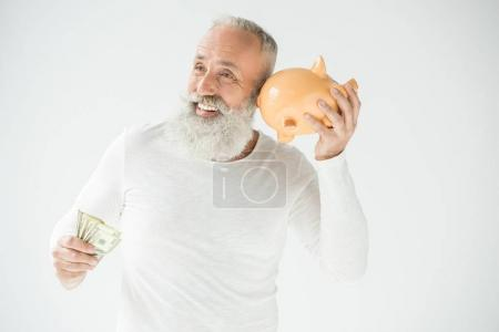 Photo for Smiling senior bearded man with dollar banknotes and piggy bank, isolated on white - Royalty Free Image