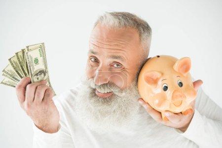 Photo pour Homme barbu âgé heureux avec des billets en dollars et tirelire, isolé sur blanc - image libre de droit