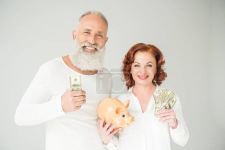 Photo for Smiling mature couple with dollar banknotes and piggy bank, isolated on white - Royalty Free Image