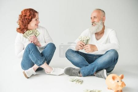 Photo for Happy mature couple with dollar banknotes and piggy bank, isolated on white - Royalty Free Image