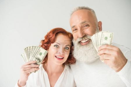 Photo pour Couple d'âge mûr souriant avec des billets en dollars, isolé sur blanc - image libre de droit