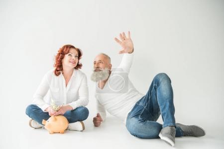 Photo pour Couple mature souriant rêvant avec des billets en dollars et tirelire, isolé sur blanc - image libre de droit
