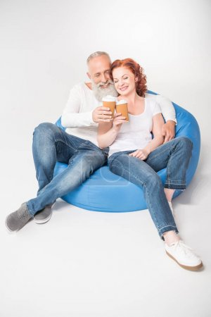 Photo for Happy mature couple drinking coffee from disposable cups while sitting in bean bag chair, isolated on white - Royalty Free Image