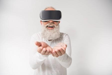 Photo for Senior bearded man gesturing and using virtual reality headset, isolated on white - Royalty Free Image