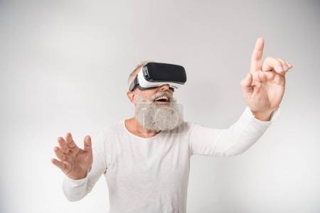 Photo for Senior excited man gesturing and using virtual reality headset, isolated on white - Royalty Free Image