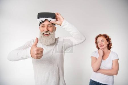 Photo for Smiling senior man using virtual reality headset and showing thumb up, isolated on white - Royalty Free Image