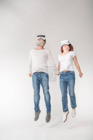 Photo for Senior couple jumping while using virtual reality headsets, isolated on white - Royalty Free Image