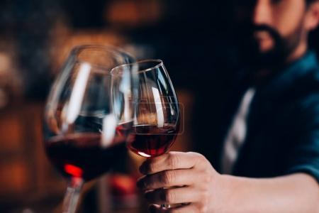 Photo for Close-up partial view of friends clinking glasses of red wine - Royalty Free Image