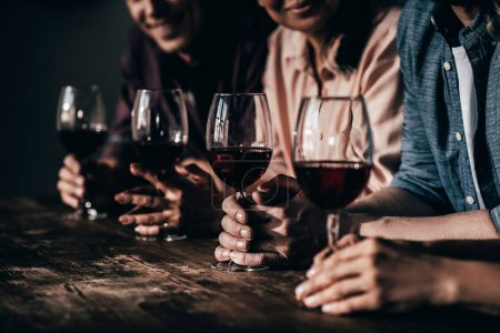 Photo for Cropped shot of smiling friends drinking red wine together - Royalty Free Image