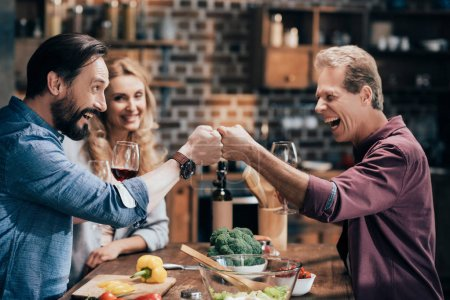 Photo for Side view of cheerful mature men smiling each other while drinking wine together in kitchen - Royalty Free Image