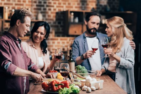 Photo for Cheerful multiethnic friends cooking dinner and drinking wine together - Royalty Free Image