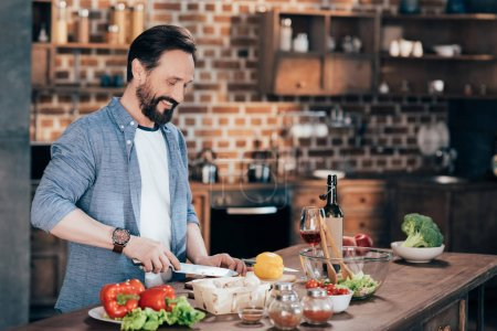 Photo for Smiling mature bearded man preparing vegetable salad at home - Royalty Free Image