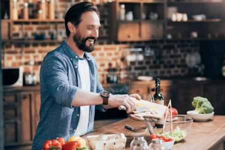 Photo for Smiling bearded man cooking vegetable salad in kitchen - Royalty Free Image