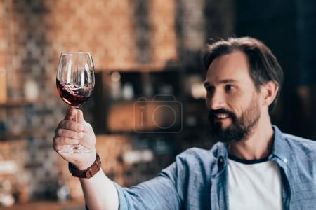 man examining red wine