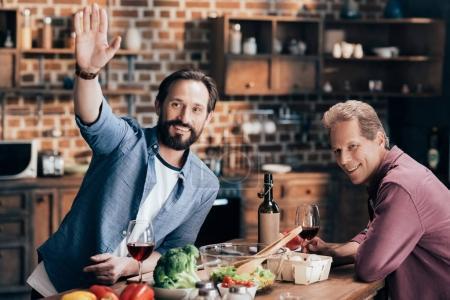 men drinking wine in kitchen