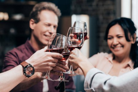 Photo for Cropped shot of middle aged friends clinking glasses with red wine - Royalty Free Image