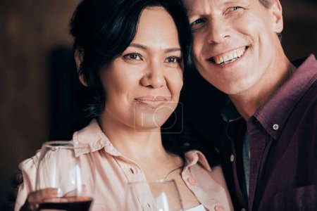 Photo for Handsome smiling man and beautiful woman with glasses of red wine looking away together - Royalty Free Image