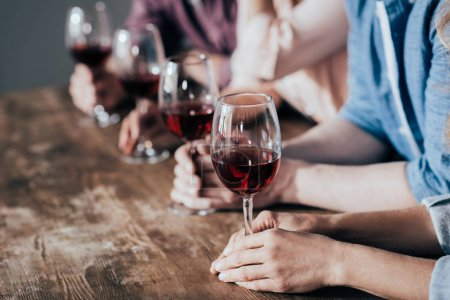 Photo for Cropped shot of people sitting in row and holding glasses of red wine - Royalty Free Image