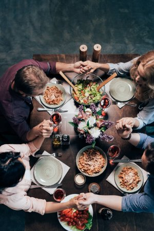 friends praying before dinner
