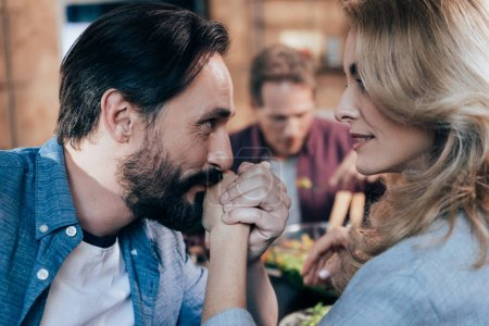 man kissing hand of woman
