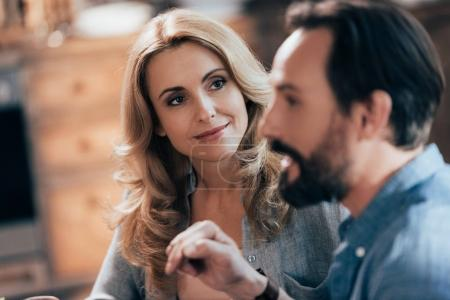 Photo for Beautiful blonde woman smiling and looking at bearded man on foreground - Royalty Free Image