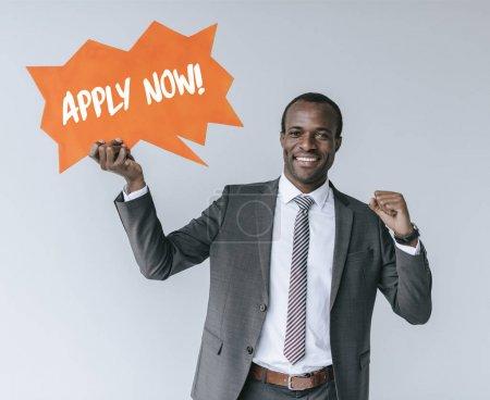 Photo pour Portrait de souriant homme d'affaires afro-américain avec appliquer maintenant carte isolée sur gris - image libre de droit